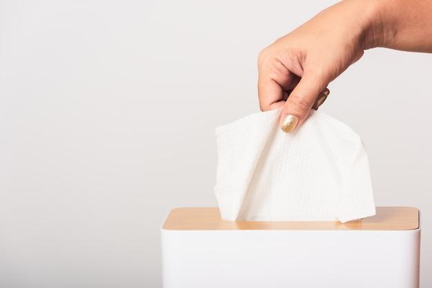 Prendre la main en tirant les mouchoirs blancs hors d'une boîte blanche