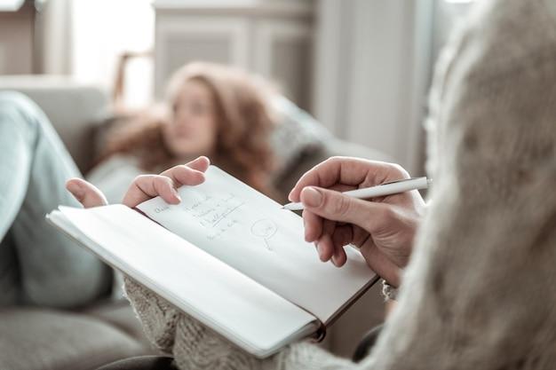 Prendre des notes. gros plan sur un psychologue professionnel prenant des notes en écoutant un client stressé