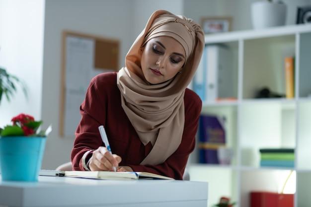 Prendre des notes. jeune femme séduisante avec du maquillage naturel prenant des notes tout en travaillant