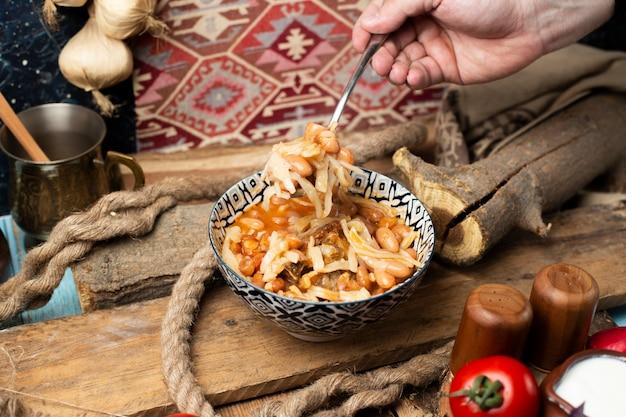 Prendre des nouilles de haricots dans un bol avec une cuillère.