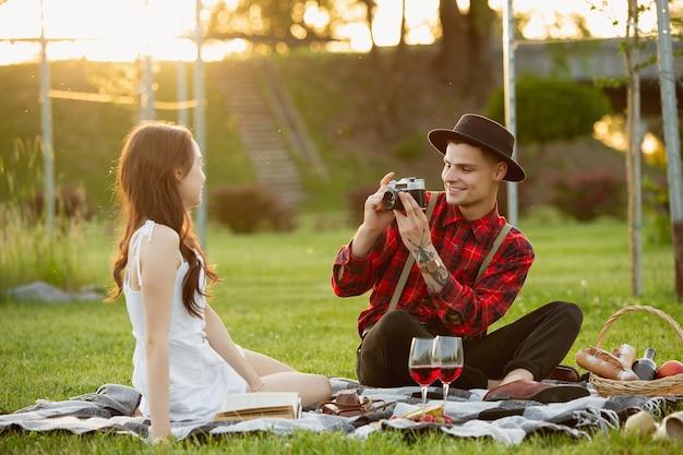 Prendre une photo. jeune couple caucasien profitant d'un week-end ensemble dans le parc le jour de l'été. regardez belle, heureuse, joyeuse. concept d'amour, de relation, de bien-être, de style de vie. des émotions sincères.