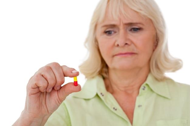 Prendre la pilule. une femme âgée réfléchie tenant une pilule dans sa main et la regardant tout en étant isolée sur fond blanc