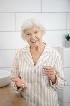 Prendre des pilules. femme en pyjama tenant une pilule dans ses mains et un verre d'eau