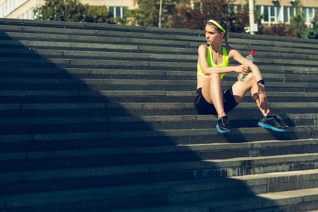 Prendre une respiration athlète féminine s'entraînant à l'extérieur