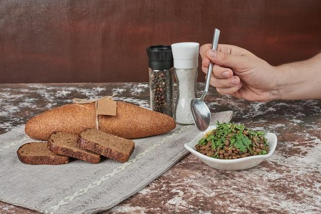 Prendre une salade de haricots avec une cuillère.