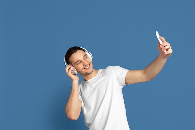 Prendre selfie, écouter de la musique. portrait du jeune homme caucasien sur le mur bleu du studio.