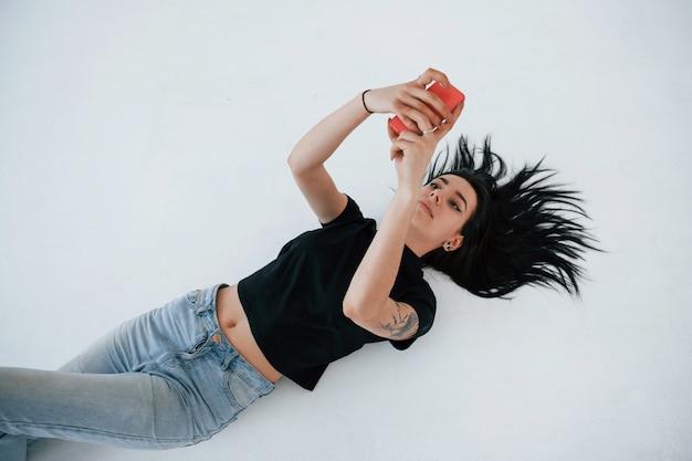 Prendre un selfie. une jeune adolescente brune a une séance photo en studio pendant la journée