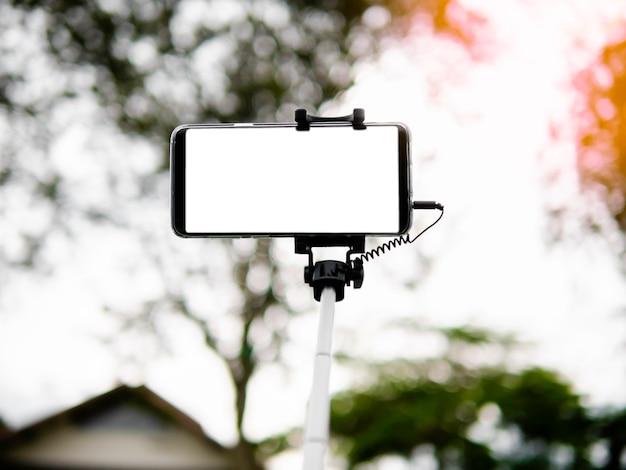 Prendre selfie par smartphone avec selfie bâton sur fond flou, montrant un écran blanc