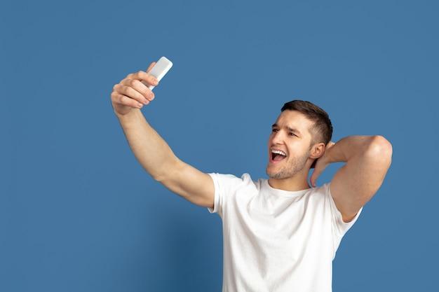 Prendre un selfie. portrait de jeune homme caucasien isolé sur le mur bleu du studio.