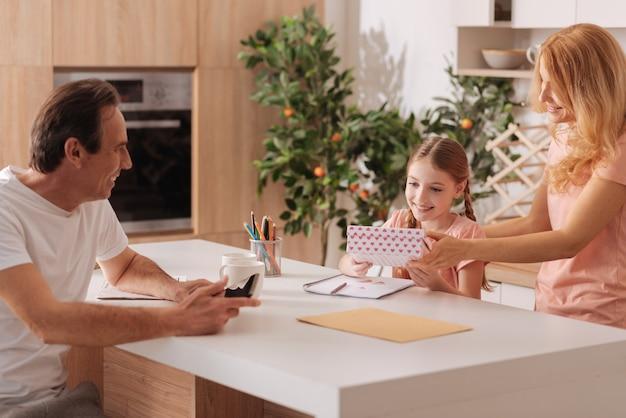 Prendre soin de joyeux père joyeux profitant de vacances en famille à la maison et en utilisant un gadget électronique pendant que la femme donne un cadeau à la fille