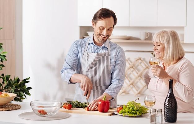 Prendre soin de ma mère. charmant fils qualifié positif debout dans la cuisine et la cuisson de la salade de légumes tandis que sa mère âgée de boire du vin