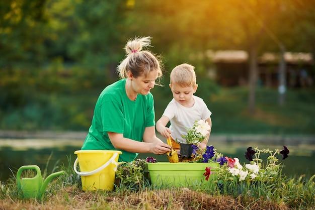 Prendre soin de la nature. mère et fils planter des semis dans le sol sur l'attribution sur la rive du fleuve. concept botanique et écologique.
