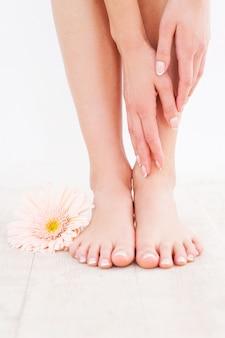 Prendre soin de ses pieds. gros plan d'une jeune femme touchant ses pieds en se tenant debout sur un plancher de bois franc