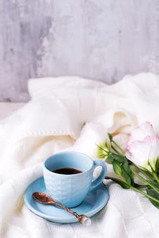 Prendre une tasse de café avec du chocolat, des fleurs eustoma sur une couverture au lit.
