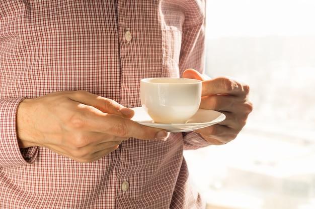 Prendre une tasse de café le matin près de la fenêtre