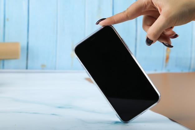 Prendre un téléphone portable noir avec un doigt