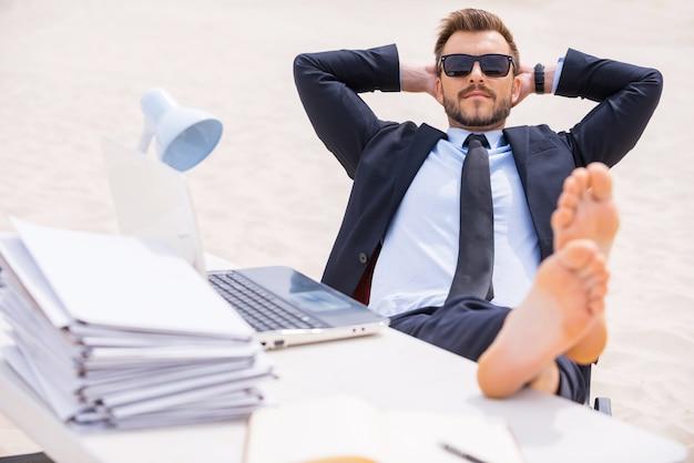 Prendre le temps de se détendre. jeune homme détendu en tenues de soirée et lunettes de soleil tenant les mains derrière la tête et tenant ses pieds sur la table debout sur le sable