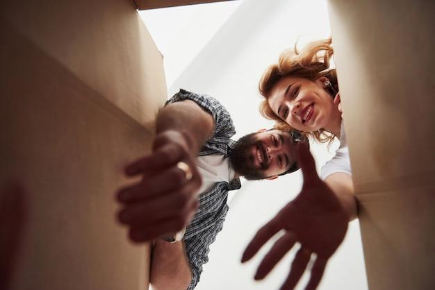 Prendre les vêtements de la boîte. heureux couple ensemble dans leur nouvelle maison. conception du déménagement
