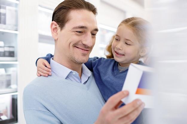 Prends papa. homme confiant énergique tenant une fille et la sélection de médicaments