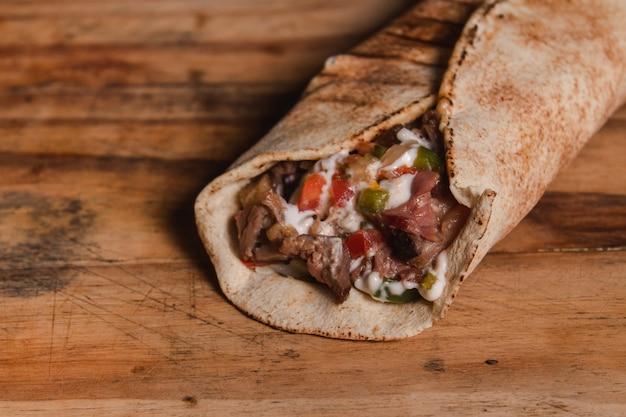 Prenez le détail d'un filet arabe farci de sauces sur une table en bois.