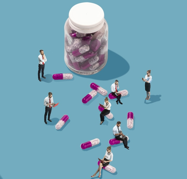 Prenez des pilules pour récupérer. vue grand angle d'un bureau moderne et créatif sur fond bleu - grandes choses et petits travailleurs. travail de bureau, tâche quotidienne, problèmes typiques et concept de style de vie. collage.