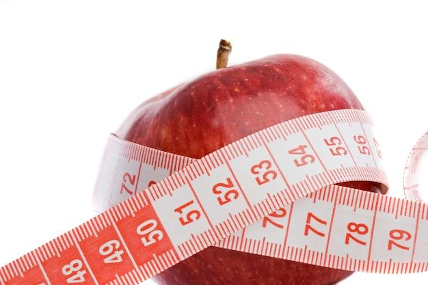 Prenez soin de votre silhouette et de votre santé. une pomme rouge avec du ruban adhésif