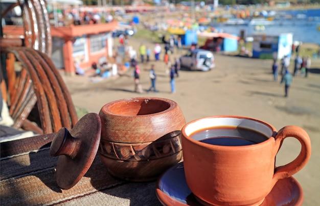 Prenez une tasse de café sur la terrasse extérieure à l'étage supérieur du café au bord de l'eau