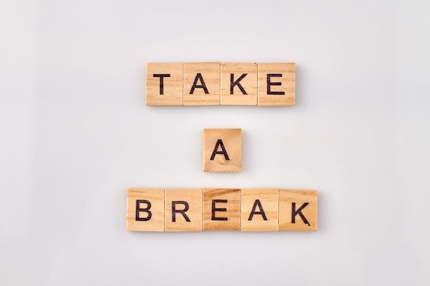 Prenez un texte de pause sur des cubes sur fond blanc. il est temps de se détendre et d'arrêter le travail.