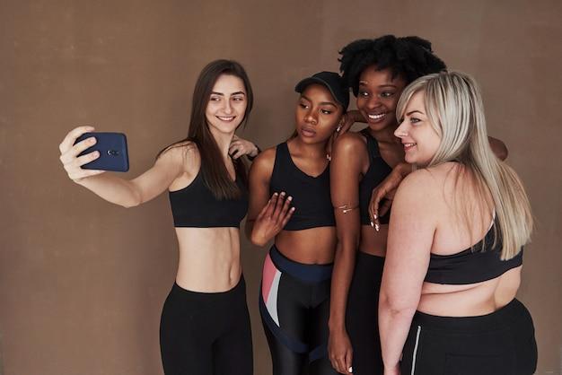 Prenons une photo. groupe de femmes multiethniques debout contre l'espace brun