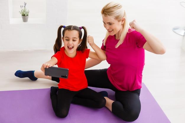 Prenons une photo pour le réseau social. portrait en gros plan d'une belle mère et d'une fille tendre douce et sportive portant des vêtements de sport faisant un appel vidéo via une connexion internet