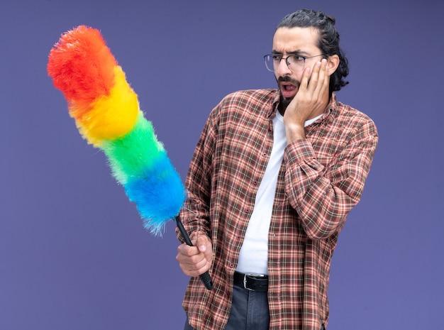 Préoccupé jeune beau mec de nettoyage portant t-shirt tenant et regardant plumeau mettre la main sur la joue isolé sur le mur bleu