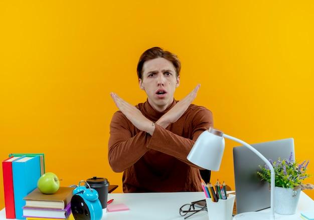 Préoccupé jeune étudiant garçon assis au bureau avec des outils scolaires montrant le geste de non