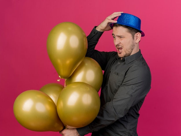 Préoccupé jeune homme de fête portant un chapeau bleu tenant et regardant des ballons mettant la main sur un chapeau isolé sur rose