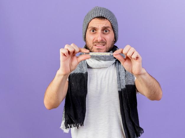 Préoccupé jeune homme malade portant un chapeau d'hiver avec écharpe tenant un thermomètre isolé sur violet