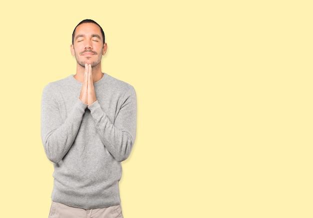Préoccupé jeune homme priant le geste