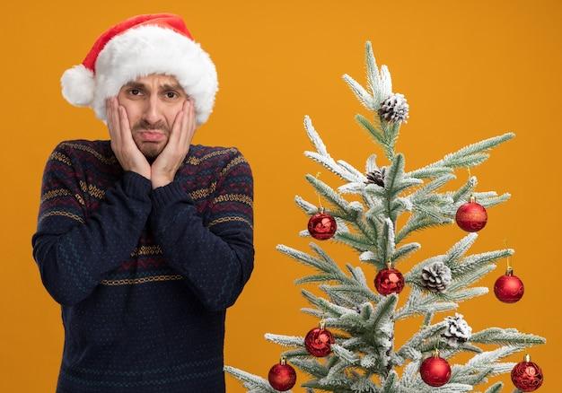 Préoccupé jeune homme de race blanche portant un chapeau de noël debout près de l'arbre de noël décoré en gardant les mains sur le visage en regardant la caméra isolée sur fond orange