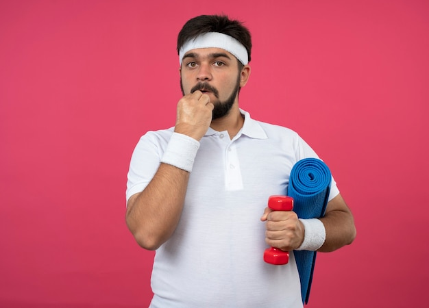 Préoccupé jeune homme sportif portant un bandeau et un bracelet tenant un haltère avec un tapis de yoga mettant la main sur le menton