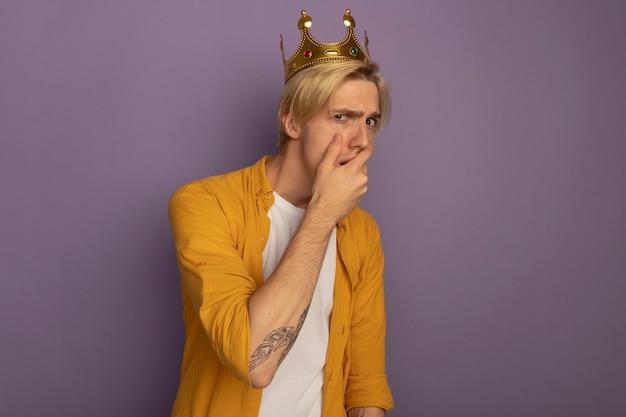 Préoccupé jeune mec blond portant un t-shirt jaune et la bouche couverte de couronne avec la main isolé sur violet