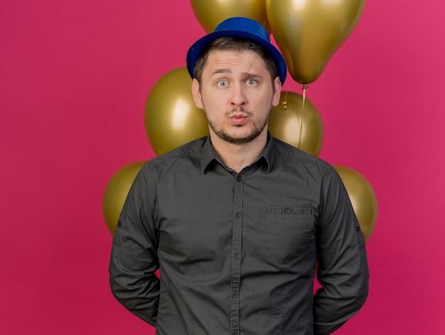 Préoccupé jeune mec portant chapeau bleu debout devant des ballons isolés sur rose