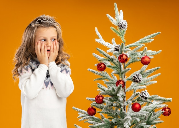 Préoccupée petite fille debout à proximité de l'arbre de noël portant diadème avec guirlande sur les joues couvertes de cou avec les mains isolés sur fond orange