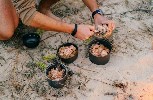 Préparation des aliments en voyage de camping. pots de nourriture dans le camp à l'extérieur. matériel touristique. tasses de voyage en métal avec céréales et viande.