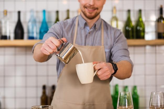 Préparation de la boisson. le lait chaud est versé dans la tasse par un barista habile professionnel lors de la préparation d'une boisson