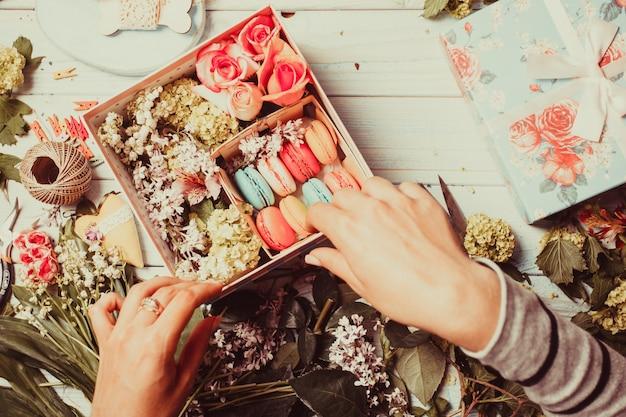 Préparation d'une boîte à fleurs avec des macarons, vue de dessus du lieu de travail du fleuriste