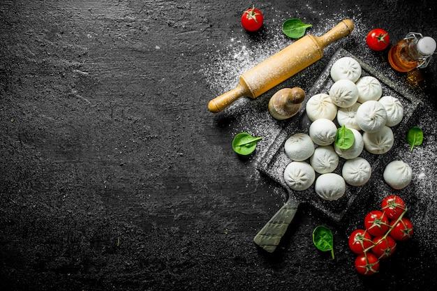 La préparation des boulettes de manta crues fraîchement sur table rustique noir