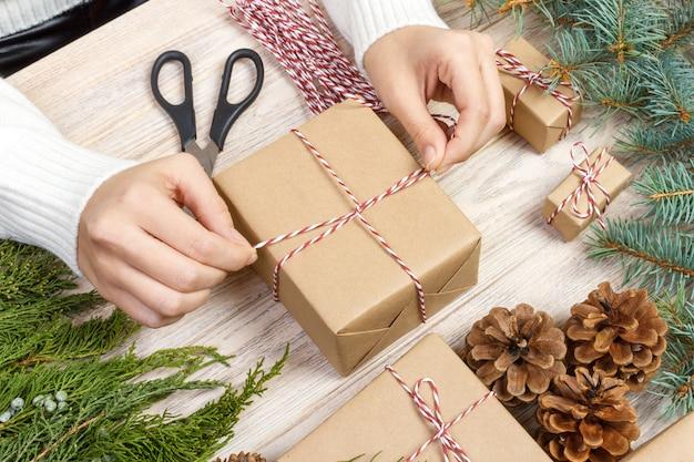 Préparation de cadeaux de noël, boîte-cadeau emballée dans du papier à rayures noir et blanc, une caisse pleine de pommes de pin et de jouets de noël et du matériel d'emballage sur du vieux bois blanc