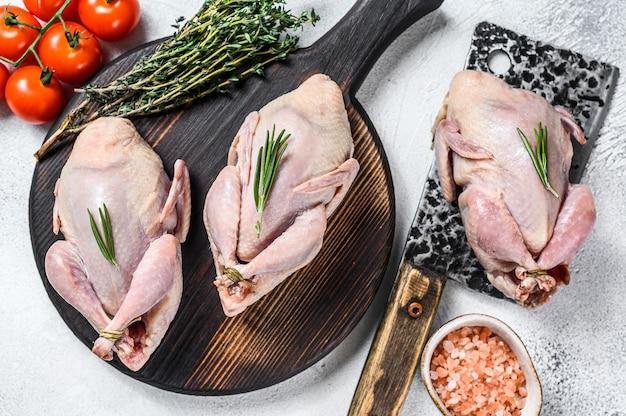 Préparation des cailles crues sur une planche à découper en bois avec couperet à viande
