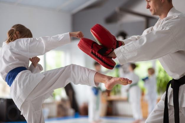 Préparation à la compétition. fille portant un kimono blanc se préparant à la compétition avec un entraîneur