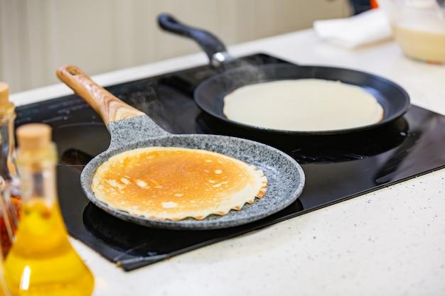 Préparation de la cuisine: le chef fait frire des crêpes fraîches dans deux casseroles