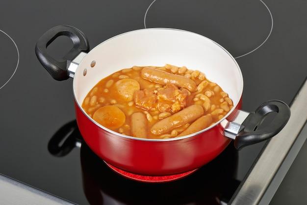Préparation du cassoulet dans un plat en céramique rouge