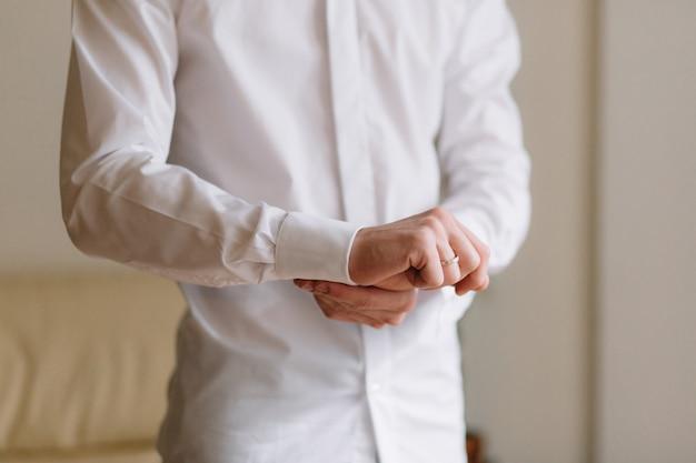 Préparation du mariage matin du marié. jeune et beau marié s'habiller dans une chemise de mariage.